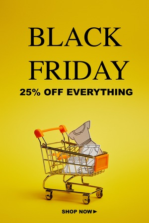 close up view of little shopping trolley with paper clothes on yellow backdrop, black friday inscription