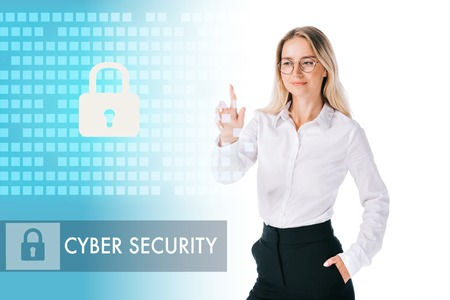 portrait of smiling businesswoman in formal wear pointing at cyber security sign isolated on white Imagens