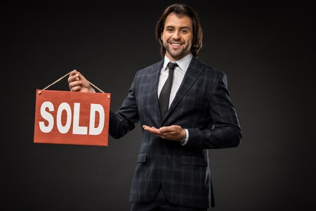professional young businessman showing sold sign and smiling at camera isolated on black