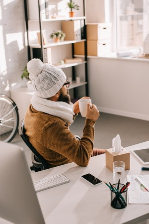 sick businessman in scarf and knitted hat sitting at office desk and holding cup of tea Фото со стока