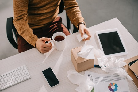 cropped view of sick businessman holding cup of tea and box of tissues at office desk