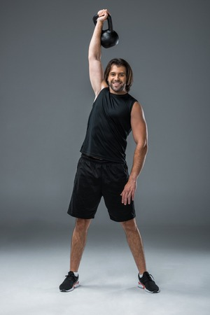 full length view of muscular young man training with kettlebell and smiling at camera on grey