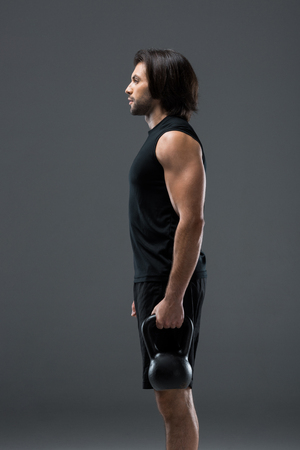 side view of athletic man holding kettlebell and looking away isolated on grey
