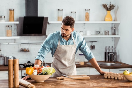 handsome young man in apron leaning at table and looking at fresh vegetables in kitchen Stock Photo