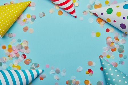 Top view of party hats and confetti on blue background