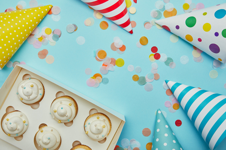 Top view of tasty cupcakes, party hats and colorful confetti on blue background Stock Photo