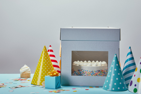 Birthday cake, party hats, gift and cupcake on table on grey background