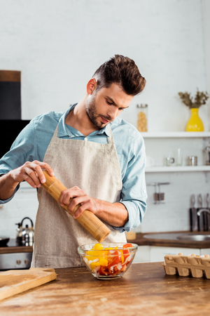 young man in apron adding pepper with mill into vegetable salad Stockfoto