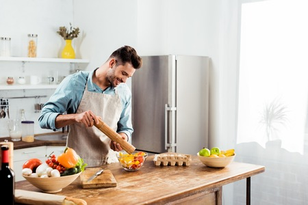 handsome smiling young man adding pepper with mill into salad