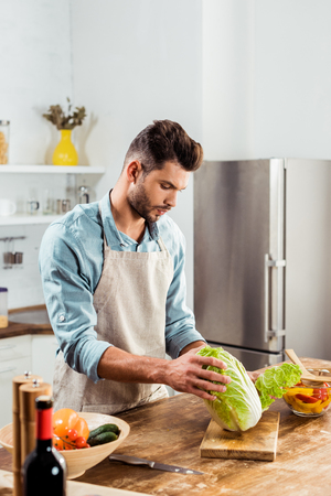 young man in apron holding napa cabbage and cooking in kitchen Stock Photo