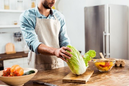 cropped shot of young man in apron holding napa cabbage and cooking in kitchen Stock Photo