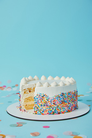 Delicious cake cut into pieces on blue background