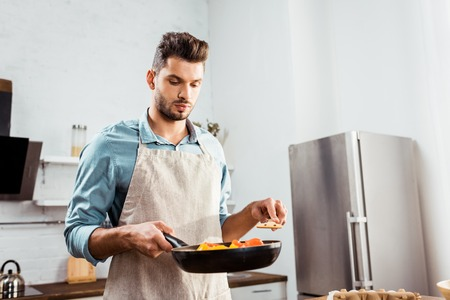 handsome young man in apron holding frying pan with vegetables