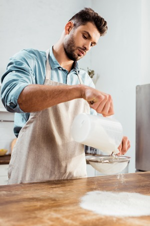 low angle view of handsome young man in apron sifting flour on kitchen table