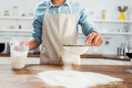 partial view of young man in apron sifting flour on kitchen table Stock Photo