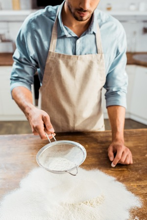 cropped shot of young man in apron sifting flour on kitchen table