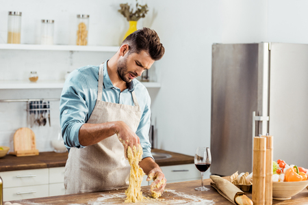 upset young man in apron looking at spoiled dough on hands