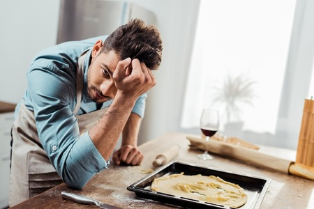upset young man in apron looking at camera while leaning at table with spoiled dough on baking tray
