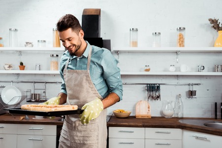 smiling young man in apron and potholders holding baking tray with fresh homemade pizza 版權商用圖片 - 112250310