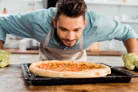 handsome smiling young man smelling fresh homemade pizza on baking tray
