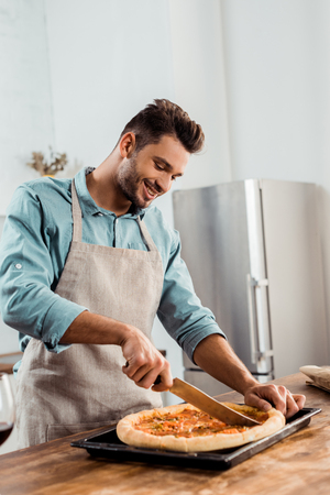 smiling young man in apron cutting fresh homemade pizza on baking tray