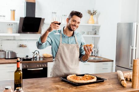 Sonriente joven en delantal sosteniendo cerca de pizza casera y copa de vino