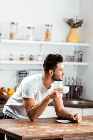 smiling young man holding cup of coffee and looking away in kitchen at morning