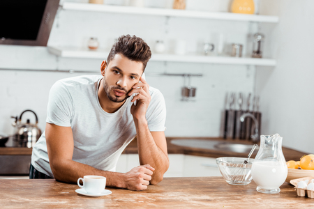 young man leaning at kitchen table and talking by smartphone at morning Stock Photo - 112250360