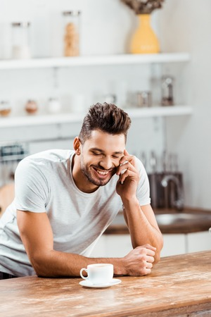 smiling young man talking by smartphone while leaning at kitchen table with cup of coffee Stock Photo - 112250365