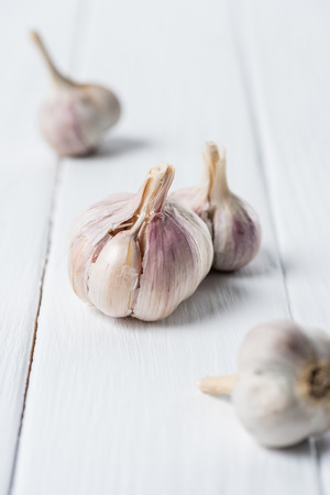 Several garlic bulbs on white wooden table Imagens