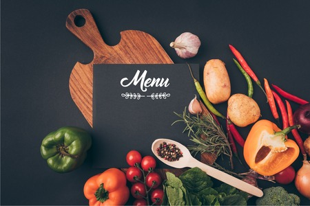 top view of black board with menu lettering on wooden table with vegetables on gray table