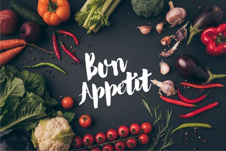 top view of unprocessed vegetables on gray table with bon appetit lettering Фото со стока