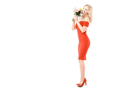 Beautiful young woman in red dress smelling flowers isolated on white Stock Photo