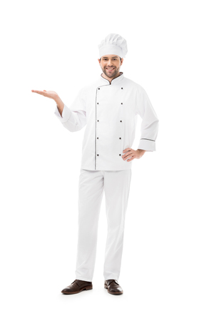 full length view of young chef showing copy space and smiling at camera isolated on white