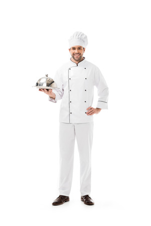 smiling young chef holding serving plate with dome and looking at camera isolated on white