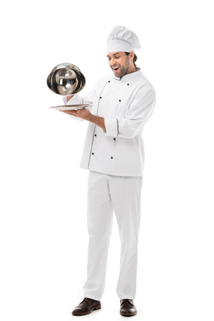 expressed young chef taking of serving dome from plate isolated on white 版權商用圖片