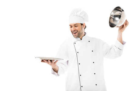 happy young chef taking of serving dome from plate isolated on white Stock fotó