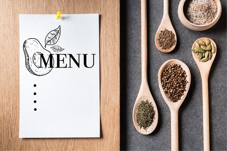 top view of dried spices on wooden spoons and paper sheet with menu inscription