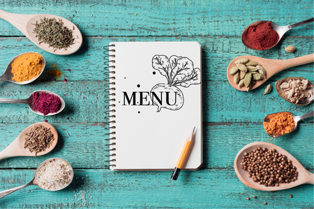top view of menu inscription in notebook with pencil and spoons with various spices on turquoise wooden surface Stock Photo