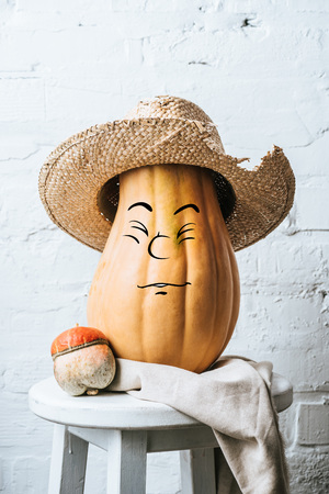 close up view of ripe pumpkins with drawn satisfaction facial expression and straw hat on wooden surface and white brick wall backdrop