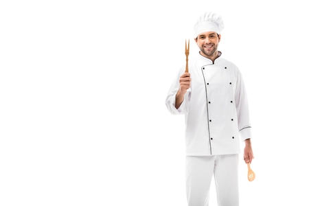 happy young chef holding kitchen utensils and looking at camera isolated on white Imagens