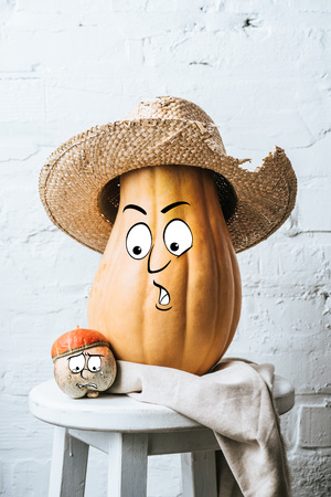 close up view of ripe pumpkins with drawn facial expressions and straw hat on wooden surface and white brick wall backdrop