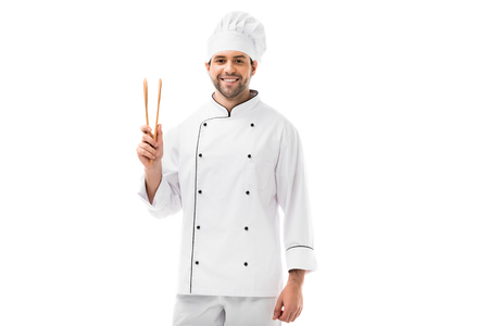 happy young chef with wooden tongs looking at camera isolated on white Stockfoto
