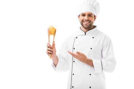 happy young chef holding pattypan squash with tongs isolated on white Stock Photo