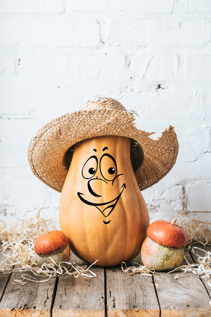 close up view of ripe pumpkins with drawn smiling facial expression and straw hat on wooden surface and white brick wall backdrop