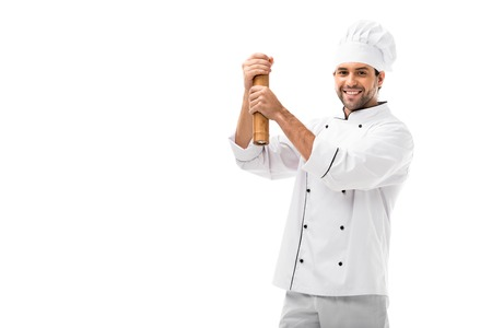 smiling young chef using bamboo pepper mill isolated on white