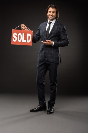 professional young businessman showing sold sign and smiling at camera on black
