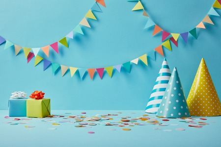party hats, confetti and gifts on blue background with colorful bunting 版權商用圖片