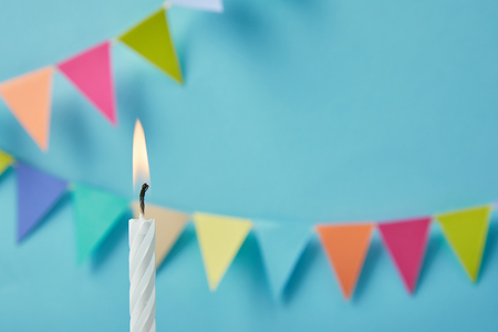 Candle on blue background with bunting