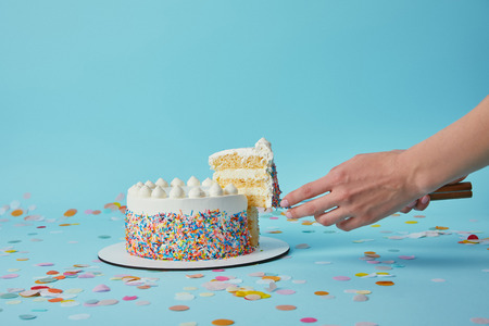Partial view of woman taking piece of delicious cake on blue background